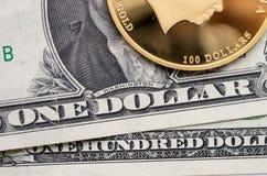 Guld- mynt med ett nominellt värde av 100 dollar och dollarräkningar Royaltyfria Foton