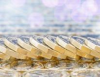 Guld- mynt med ljusa effekter Stupad bunt, bokeh Arkivbild