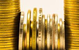 Guld- mynt och mynt som staplas i de i olik positi Arkivfoton