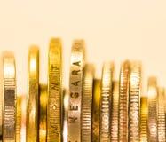 Guld- mynt och mynt som staplas i de i olik positi Arkivbilder