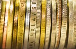 Guld- mynt och mynt som staplas i de i olik positi Arkivfoto