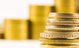 Guld- mynt och mynt staplade ineach annan i olik positi Royaltyfri Fotografi