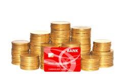Guld- mynt och röd kreditkort som isoleras på vit Royaltyfri Bild