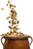 Guld- mynt som faller i tappningkrukan Arkivfoton