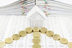 Guld- mynt som pil framme av huset Arkivfoton