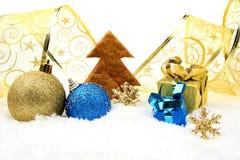 Guld- och blå julgarnering på snö med kakaträdet Royaltyfri Bild