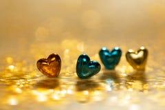 Guld- och blåtthjärtor på en mousserande guld- bakgrund Selektivt fokusera Royaltyfria Foton
