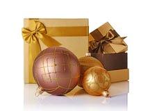 Guld- och bruna klassiska gåvaaskar med satängpilbågar och glass julbollar Arkivbilder