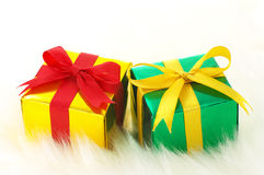 Guld och gröna gåvor på white fejkar päls. royaltyfria bilder