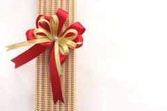 Guld- och röd bandpilbåge med giftbox på vit bakgrund Fotografering för Bildbyråer