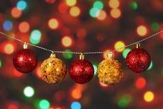 Guld- och röd jul klumpa ihop sig på den defocused bakgrunden Royaltyfri Fotografi