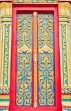 Guld- och röd thailändsk tempeldörrskulptur Arkivfoto