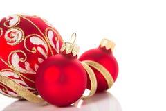 Guld- och röda julprydnader på vit bakgrund Glad julkort Fotografering för Bildbyråer