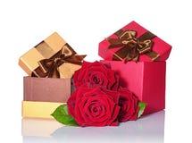 Guld- och röda klassiska skinande gåvaaskar med bruna satängpilbågar och buketten av rosor Arkivfoton