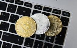 Guld- och silverbitcoinmynt på en bärbar dator svärtar tangentbordet Digital valuta faktiska pengar Metallmynt av bitcoin Fotografering för Bildbyråer