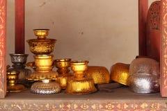 Guld- och silverbunkar är pålagda en hylla i borggården av en buddistisk tempel (Thailand) royaltyfri foto