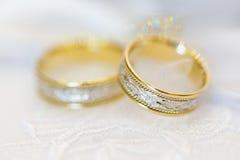 Guld- och silvervigselringar med den invecklade modellen Royaltyfri Foto