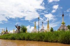 Guld- och vita buddistiska stupas på bankerna av Inle sjön Arkivfoton