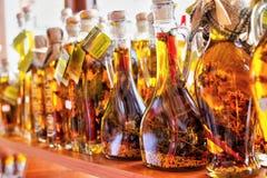 Guld- olivolja med kryddor i flaskor i Grekland arkivbilder
