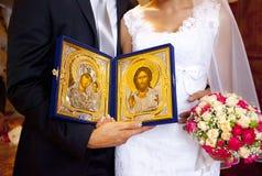 Guld- ortodoxa symboler av oskulden och Jesus i händer av bruden och brudgummen Royaltyfria Bilder
