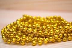 Guld- pärlor på en trätabell Guld- smycken beads guld- Royaltyfri Fotografi