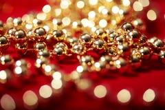 Guld- pärlor på rött med suddig ljusbokeh Royaltyfri Foto