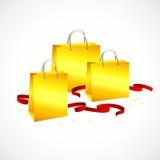 Guld- påse, rött band och stjärnor för shopping Arkivfoto