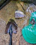 Guld- panna och skyffel i guld- rik flodbädd Arkivbild
