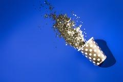 Guld- pappers- kopp för födelsedagparti med guld- konfettier på blå bakgrund royaltyfria foton