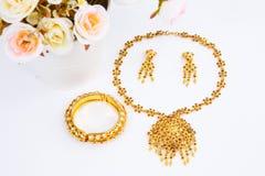 Guld- par av örhängen, guld- halsband och guld- armband på arkivbild