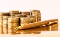 Guld- penna med guld- mynt på tabellen Royaltyfri Bild