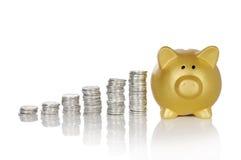 Guld- Piggybank med mynt Fotografering för Bildbyråer
