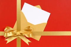 Guld- pilbåge för julgåvaband, röd bakgrund med det tomma hälsningskortet Arkivbild