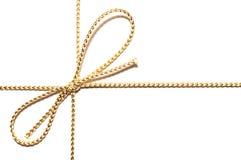 Guld- pilbåge med gåvabandsjalen för julklapp med invecklade skendetaljer som isoleras för att klippa ut enkel vanlig vit bakgrun arkivfoto