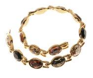 Guld pläterad halsband på en vit bakgrund Fotografering för Bildbyråer