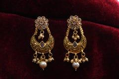Guld- pläterade smycken - önska den märkes- guld- örhängemakrobilden arkivbild