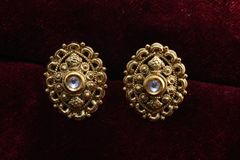 Guld- pläterade smycken - önska den märkes- guld- örhängemakrobilden arkivbilder
