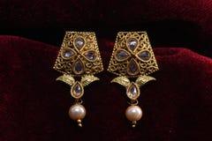 Guld- pläterade smycken - önska den märkes- guld- örhängemakrobilden arkivfoto