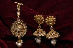 Guld- pläterade smycken - utsmyckat märkes- guld- par av örhängen och för closeupmakro för huvud den åtföljande bilden royaltyfri bild
