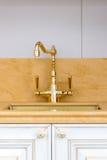 Guld- polerad kökvattenkran för tappning Royaltyfri Foto