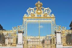 Guld- port på slotten versailles Arkivbild