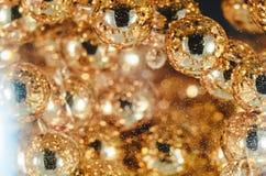 Guld pryder med pärlor i vinexponeringsglaset med vatten, bubblor, makroen, fotoet, bakgrund för design Arkivbilder