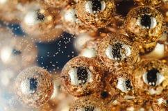 Guld pryder med pärlor i vinexponeringsglaset med vatten, bubblor, makroen, fotoet, bakgrund för design Arkivbild