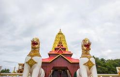 Guld- Puttakaya chedipagoda med två jätte Chinthe på ingången, Sangkhlaburi område, Kanchanaburi, Thailand Royaltyfri Bild