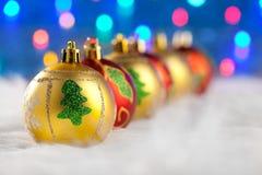 Guld- röda baubles för jul i en rad med lampor Royaltyfri Bild