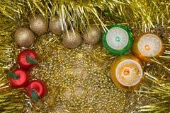 Guld-, röda, gröna och gula nytt års- eller julstruntsaker på guld- grund med guld- trasig garnering royaltyfri fotografi