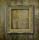 Guld- ram på grungeträväggen Arkivbild