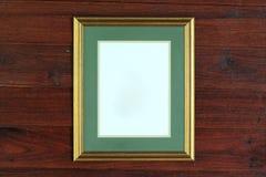 Guld- ramfoto på den wood väggen Arkivbilder