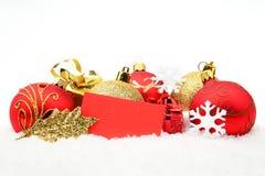 Guld- röd julgarnering på snö med önskakortet Royaltyfri Bild