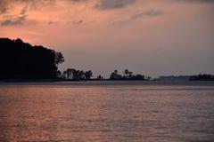 Guld- rosa färger för solnedgång på sjön i liknande färger Arkivfoto